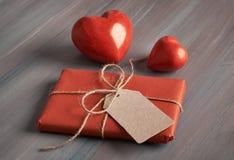 Обернутый подарок с биркой чистого листа бумаги и 2 красными каменными сердцами Стоковое фото RF