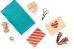 Обернуть подарок Коробка, бумага kraft, конверт, тонкий шнур, поздравительная открытка, лента, sciccors на белом взгляд сверху пр стоковое фото