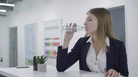 Обеспокоеная внимательная молодая дама в официальных одеждах работая с бумагами в положении офиса на счетчике Женщина с сток-видео