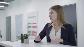 Обеспокоеная внимательная молодая дама в официальных одеждах внимательно проверяя бумаги в положении офиса на счетчике сток-видео
