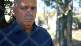 Обеспокоеный человек выглядя грустное сквозным металлическая загородка от зоны защиты акции видеоматериалы