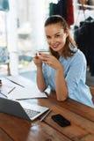 обед вопроса кофейной чашки дела сподручный раскрыл сверх Здоровая усмехаясь женщина есть суп, работая на компьютере Стоковое фото RF