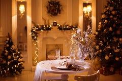 Обеденный стол в больших квартирах с украшенными рождественскими елками Стоковые Изображения