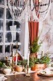 Обеденный стол украшенный для рождества и centerpiece вечнозелёного растения Стоковое Фото