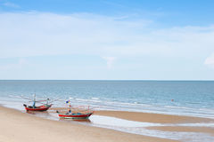 Обе из деревянной рыбацкой лодки на пляже с голубым небом Стоковые Изображения