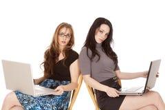 обе компьтер-книжки смотря 2 женщин стоковые изображения
