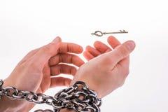 Обе прикованных руки и ключ Стоковая Фотография