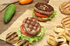 Обед с домодельными гамбургерами зажаренными BBQ на кухонном столе Стоковая Фотография