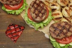 Обед с домодельными гамбургерами зажаренными BBQ на столе для пикника Стоковое Фото
