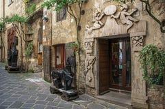 Обзор узкого прохода с старыми зданиями и деревянными скульптурами на Orvieto стоковое фото rf