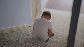 Обиденный ребенок сидя на лестницах сток-видео