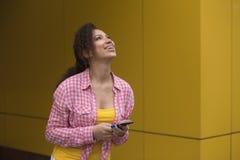 Обильная молодая женщина веселя на хороших новостях на ее мобильном телефоне и пробивая воздух с ее кулаком на городской улице стоковое фото rf