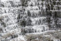 Обильный пропускать водопада каскадируя утеса в много малых ярусов Стоковое фото RF