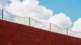 Облака бежать свободная внешняя стена тюрьмы с колючей проволокой в timelapse сток-видео