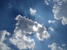 Облака в голубом небе с лучами солнца Стоковые Изображения