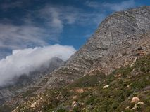 Облака завивая над горой покрывают вдоль западного побережья накидки в Южной Африке Стоковая Фотография