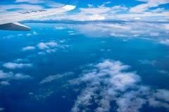 Облака и берег увиденные сверху от самолета окна стоковое фото