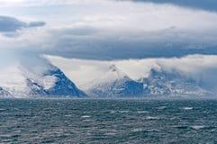Облака и пики шторма в высоком ледовитом фьорде стоковое изображение rf