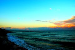 Облака нижнего яруса над развевая морем во время захода солнца стоковое фото
