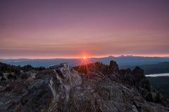 Облака освещают - пурпур над Sunburst на пике Paulina Стоковые Фотографии RF