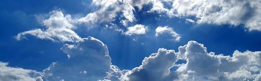 Облака отражают свет в ярком голубом небе стоковое фото rf