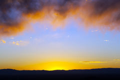облака предпосылки обрамили заход солнца Стоковое Фото