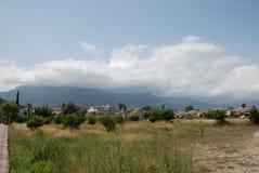 Облака спускают под горными пиками над городом горы стоковая фотография