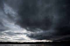 Облака с предпосылкой, солнечным светом через очень темную предпосылку облаков темного облака шторма Стоковое Изображение