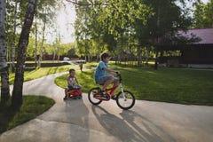 Область Москвы, Россия - 2-ое июня 2014 3 брать мальчика имеют потеху играя в сельской местности на солнечном вечере лета Стоковое фото RF