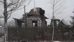 Область России, Ленинград, Nikolskoye, 14-ое декабря 2018 - трактор Volvo сокрушает частный деревянный дом, разбирая здание видеоматериал