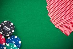 Обломоки казино и карты покера на зеленом войлоке, предпосылке стоковое фото rf