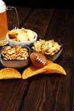 Обломоки, соленые закуски, футбол и пиво на таблице Большой для проектов игры шара стоковые фотографии rf
