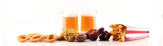 Обломоки, соленые закуски, футбол и пиво на таблице Большой для проектов игры шара стоковая фотография rf