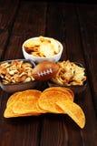 Обломоки, соленые закуски, футбол на таблице Большой для игры шара стоковые изображения