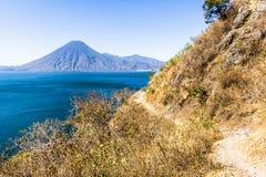 Обматывая тропа clifftop грязи, вид на озеро & вулкан, озеро Atitlan, Гватемала стоковые фотографии rf