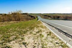 Обматывая шоссе протягивая в расстояние против фона красивого ландшафта весны, полей, лугов, лесов и стоковые изображения