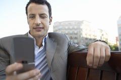 Обмен текстовыми сообщениями бизнесмена на мобильном телефоне Outdoors Стоковая Фотография RF
