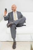 Обмен текстовыми сообщениями бизнесмена на софе дома Стоковые Фото