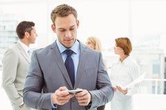Обмен текстовыми сообщениями бизнесмена с коллегами в встрече позади Стоковое фото RF
