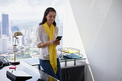 Обмен текстовыми сообщениями бизнес-леди на телефоне в офисе 3 Стоковое Изображение RF
