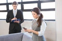 Обмен текстовыми сообщениями коммерсантки на smartphone и бизнесмене используя цифровую таблетку Стоковое Изображение