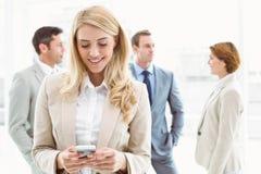 Обмен текстовыми сообщениями коммерсантки с коллегами в встрече позади Стоковое Изображение RF