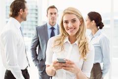 Обмен текстовыми сообщениями коммерсантки с коллегами в встрече позади Стоковое Изображение