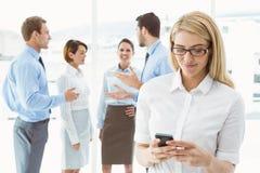 Обмен текстовыми сообщениями коммерсантки с коллегами в встрече позади Стоковая Фотография