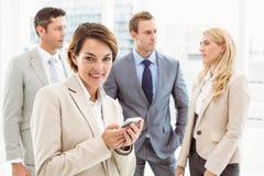 Обмен текстовыми сообщениями коммерсантки с коллегами в встрече позади Стоковое Фото