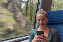 Обмен текстовыми сообщениями молодой женщины с его смартфоном во время путешествия в поезде пока она идет работать стоковая фотография rf
