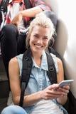Обмен текстовыми сообщениями молодой женщины на мобильном телефоне Стоковая Фотография