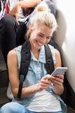 Обмен текстовыми сообщениями молодой женщины на мобильном телефоне Стоковое фото RF