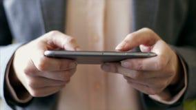 Обмен текстовыми сообщениями рук коммерсантки на умном телефоне на офисе акции видеоматериалы