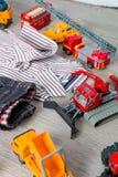 Обмундирование мальчика близко установленное игрушки автомобиля Striped рубашка, джинсовая ткань задыхается желтые и красные авто Стоковые Изображения